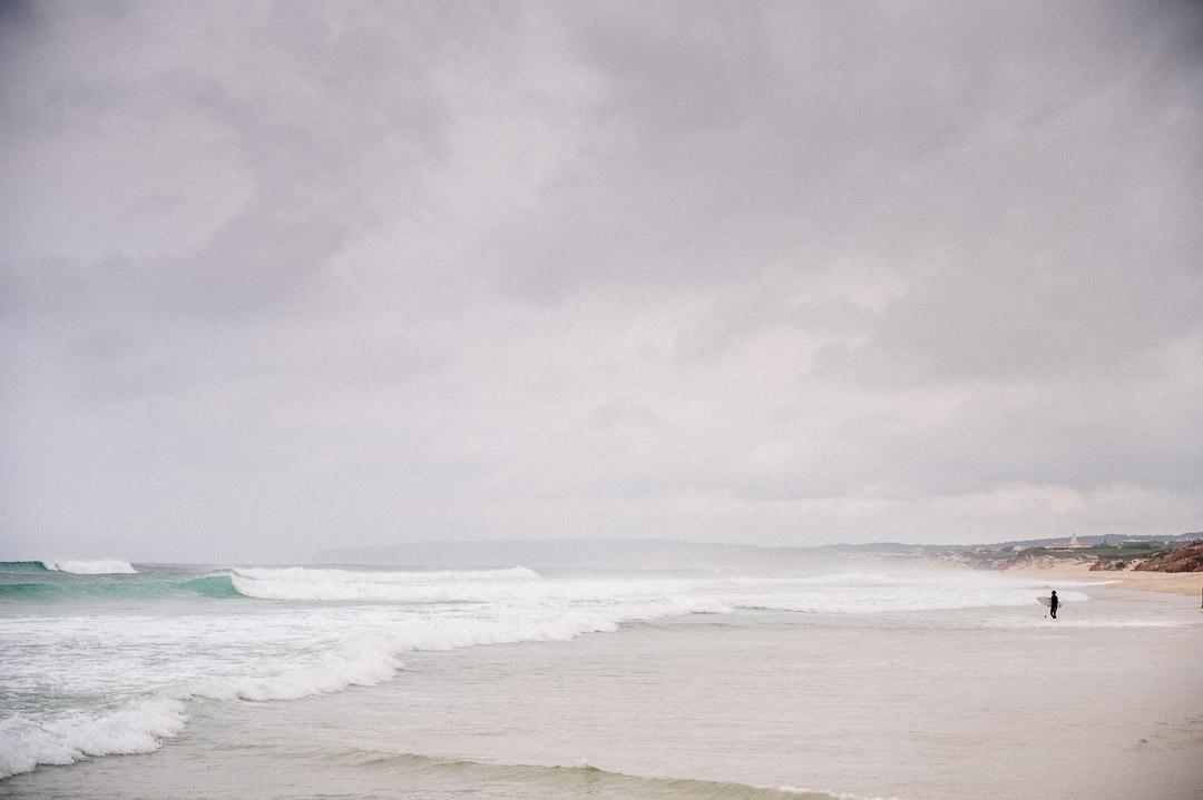 Surfer geht vom Strand ins Wasser